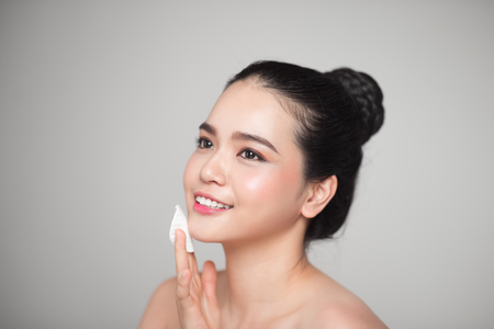 Happy smiling beautiful asian woman using cotton pad cleaning skin. 스톡 콘텐츠