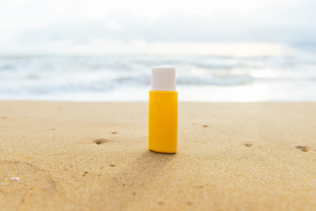 여름 일광욕. 모래에 썬 로션 병