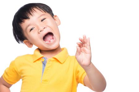 Kleiner asiatischer Junge, der seinen verlorenen Milchzahn in seiner Hand - Nahaufnahme zeigt