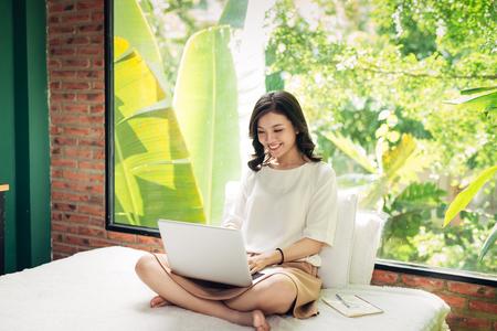 美しい若いの笑顔の女性は大きな窓の近く自宅のベッドの上に座っている間のラップトップに取り組んでいます。