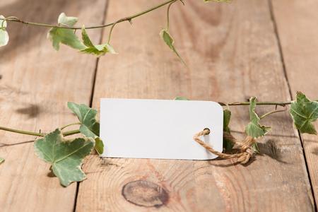 木製の背景の空白タグと緑を葉します。