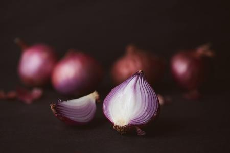 Full and half cut spanish onions on dark background.