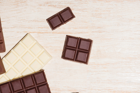 A lot of variety chocolates bar in box on white wooden background Stock Photo