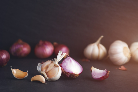 Garlic and onion on the black stone table Stockfoto