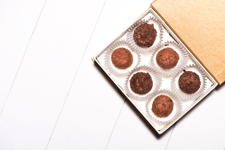 白い木製の背景のボックスに様々 なチョコレートがたくさん 写真素材