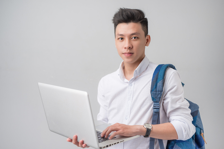 Gelukkige toevallige Aziatische mannelijke student die die laptop met behulp van op een grijze achtergrond wordt geïsoleerd