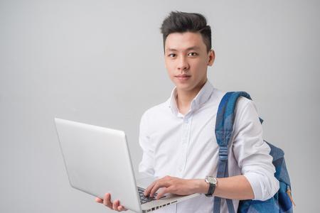 heureux décontracté étudiant mâle asiatique utilisant un ordinateur portable isolé sur un fond gris