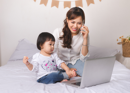 Asian lady in classic suit is talking on the mobile phone and working on laptop at home with her baby girl.