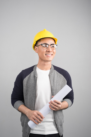Handsome civil engineer working with documents looking to the side on gray background Banco de Imagens
