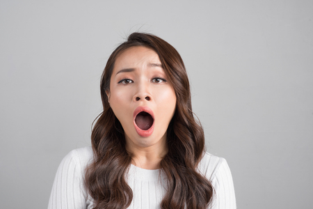 Asian woman yawns, bored, isolated on gray background