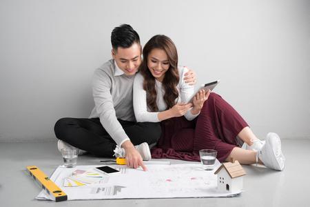 若いアジアの大人のカップルは新しい家の設計を企画・ フロールの上に座って。