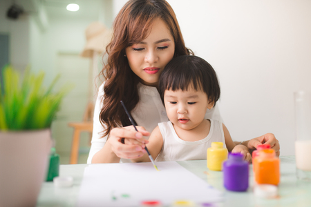 assignments: Happy family mother and daughter together paint. Asian woman helps her child girl. Stock Photo