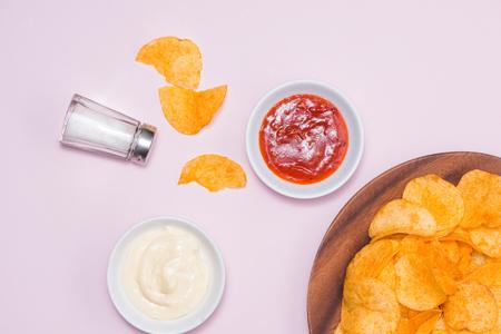 不健康な食品のコンセプトです。チーズと玉ねぎポテトチップスのピンクの背景の辛味ソースかけ。