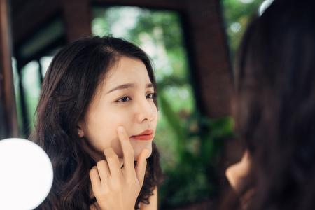 Schoonheid, huidverzorging levensstijl concept. Jonge Aziatische vrouw met acne naar de spiegel kijken.