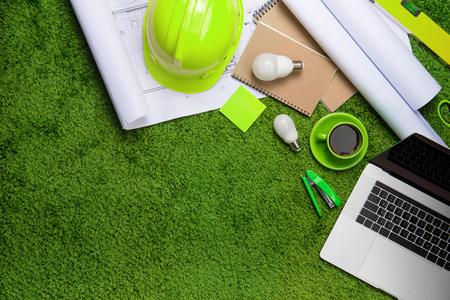 Werkplaats met helm, blauwdrukken, laptop en notitieblok op gras achtergrond. Bovenaanzicht met kopie ruimte Stockfoto