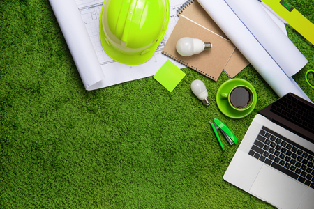 Workplace with helmet, blueprints, laptop and notepad on grass background. Top view with copy space