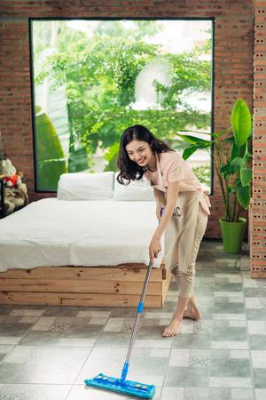 Huiswerk en huishoudelijk concept. Vrouw schoonmaak vloer met mop binnenshuis