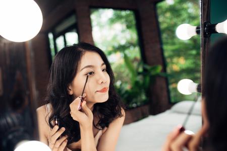自宅でまつげに黒のマスカラーを適用する鏡を見て美しい若い女性の肖像画