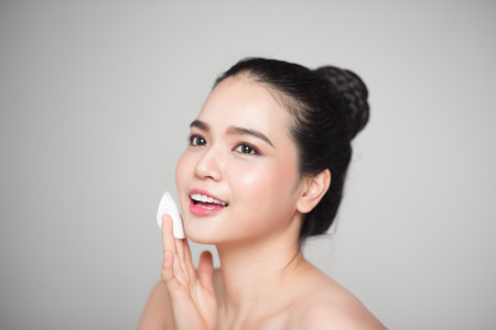 幸せ笑顔美しいアジア女性の皮膚を洗浄綿パッドを使用します。