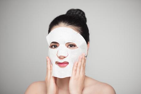 Spa, gezondheidszorg. Vrouw met zuiverend masker op haar gezicht dat op witte achtergrond wordt geïsoleerd