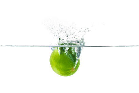 Fresh lime dropped into the water with water splash on a white background
