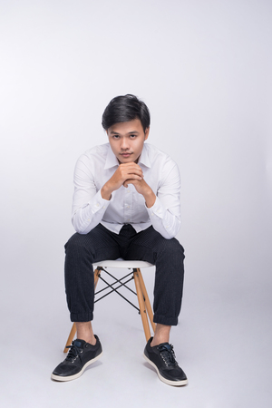 Full length of a young asian casual man sitting on a chair over white background Zdjęcie Seryjne