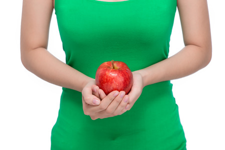 Fruit. Beautiful female hand holding and showing a red apple on white background Stock Photo