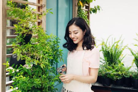 De leuke Aziatische installaties van het vrouwentuinman met tuinschaar in serre
