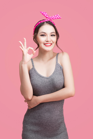 Portrait of asian girl with pretty smile in pinup style with hands gesture on pink background