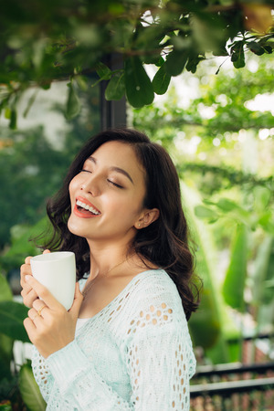 Pretty vietnamese woman enjoying her morning coffee on a veranda Stock fotó