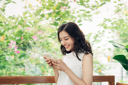 Confident young asian woman in smart casual wear typing on phone. Stock Photo