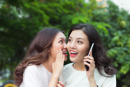 Surpried young woman whispering at a cheerful friend while on call