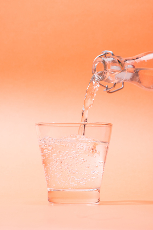 Pouring water from bottle to glass on orange background Banco de Imagens