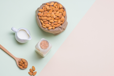 Almonds and milk bottle on light background. Almond nuts in spoon. Фото со стока