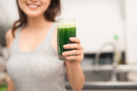 Young asian woman enjoy healthy vegetarian smoothie for weight loss and detox Фото со стока