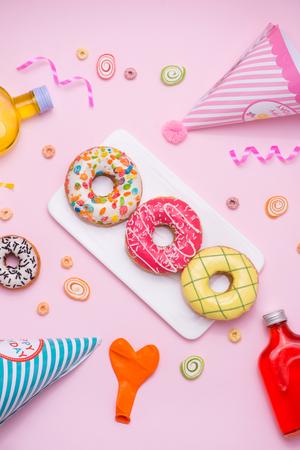 パーティー。異なるカラフルな甘い丸い艶をかけられたドーナツとピンク背景にドリンクのボトル。 写真素材
