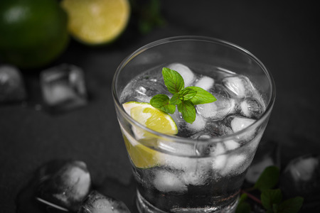 Mojito cocktail with lime and mint in glass on a grey stone background Stok Fotoğraf - 82526819