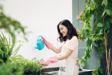 Aziatische vrouw tuinier watering de bloemen in haar tuin in de zomer