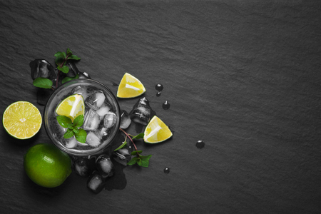 Mojito cocktail with lime and mint on dark stone table