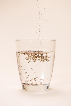 Glas water met kopje gezonde Chia zaden en lepel. Tekstruimte. Stockfoto