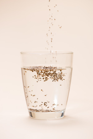 Glass of water with cup of healthy chia seeds and spoon. Text space. Stock Photo