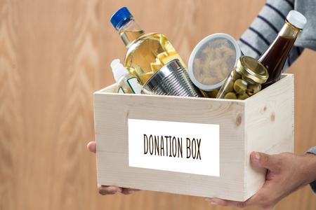 Volunteer with donation box with food stuffs on wooden background
