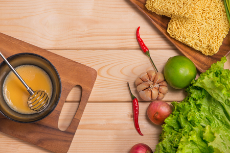spice: Instant noodles for cooking and eat in the dish with whipped egg and vegetables on wooden background.