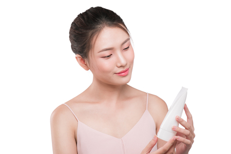 Asian young woman holding tube of moisturizer, oil, wellness, exfoliator, peeling cream in hand.