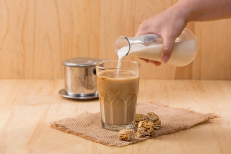 Pouring milk in to glass of coffee on a wooden table. Stock Photo