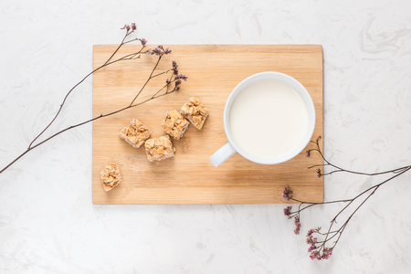 Dairy products. A cup of milk serve with almond candies on a rustic wooden table. Фото со стока