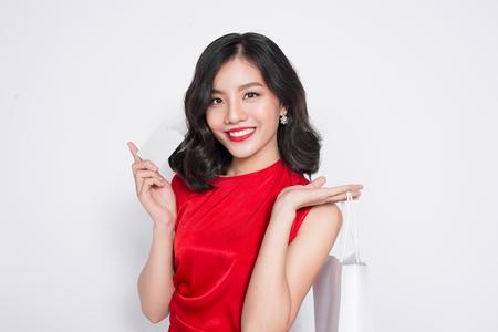 美しいアジアの女性は白で立っているショッピング バッグと赤いドレスを着てします。