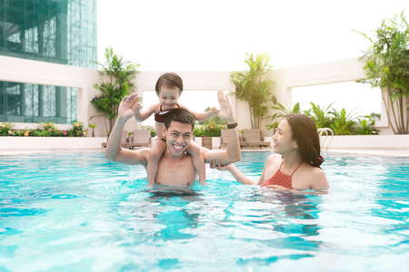 Happy family in swimming pool. Summer holidays and vacation concept
