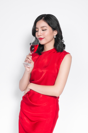 Beautiful asian girl in evening dress smiling holding glass of champagne