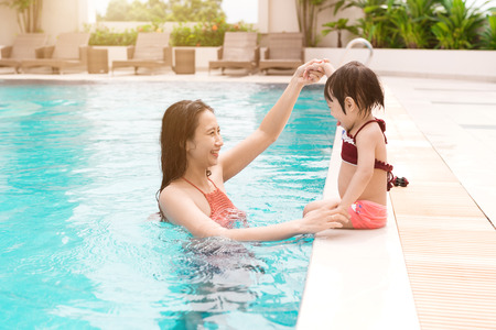 Mother and baby girl having fun in the pool. Summer holidays and vacation concept 版權商用圖片